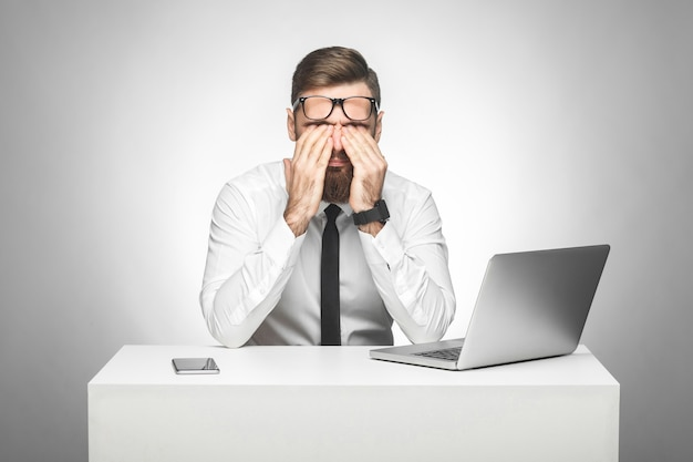 Безумно уставший молодой менеджер в белой рубашке и черном галстуке сидит в офисе, протирая глаза после долгой работы за компьютером, делает важный отчет. снимает очки. студийный снимок, изолированный, закрытый