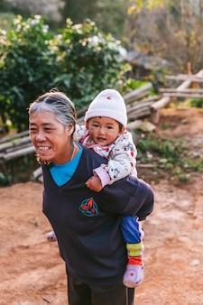 タイ北部のおばあちゃんは長袖のシャツを着て、タイのチェンマイの丘の上のmaejantaiのakha村で彼女の背中に子供を運びます。