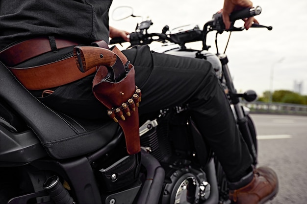 Mafia man on bike with handgun. sporty biker handsome rider male. chase in the big city.