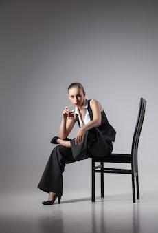 濃い灰色の背景の上のマフィアの女性。ファッション写真。レトロなスタイル