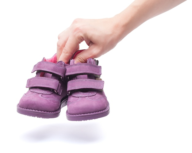 Magenta children`s boots on female hand. isolated