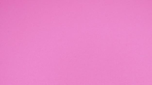 背景にマゼンタまたはピンクの紙。空きスペースで人がいません。