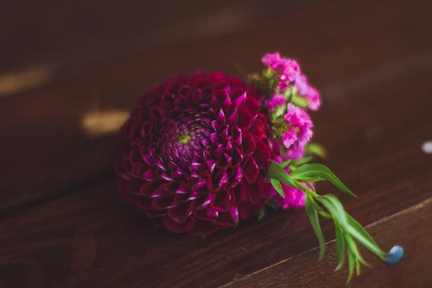 Пурпурная свадебная бутоньерка для жениха на деревянном фоне.