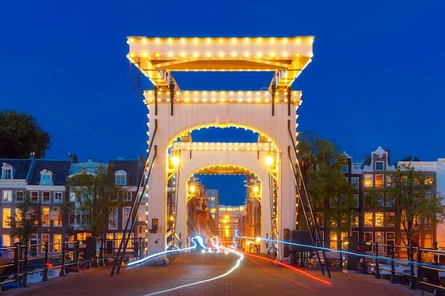 Magere brug, тощий мост с ночным освещением над рекой амстел в центре амстердама, голландия, нидерланды