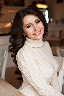カフェに座っている若い女性の魔法の驚くべき美しさ。ブルネットの夢。美しいウェーブのかかった髪、高級化粧。