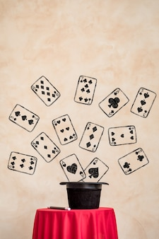 마법의 검은 모자와 빨간색 테이블에 카드 놀이