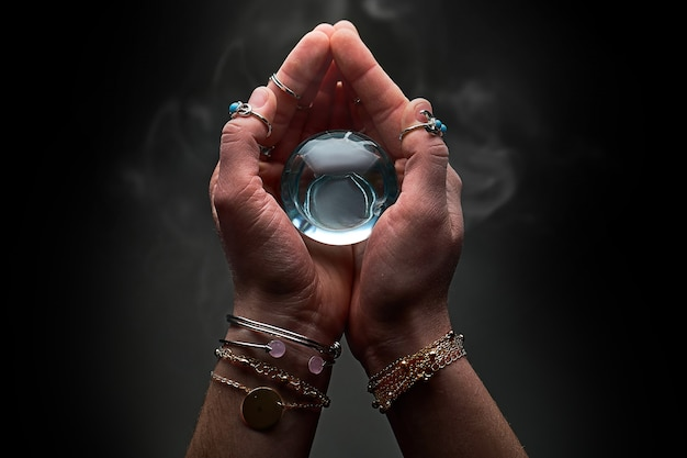 Magic blue crystal ball with smoke in hands of fortune teller for prediction and divination on a dark black wall
