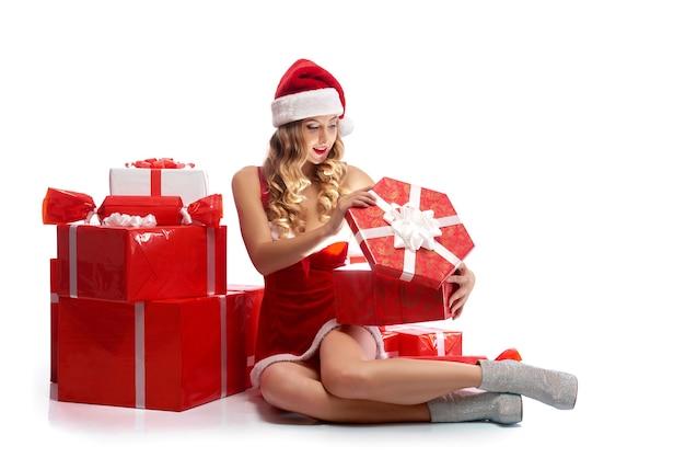 マジックボックス。孤立した魔法のプレゼントを開く陽気なセクシーなサンタの女の子の水平スタジオショット。
