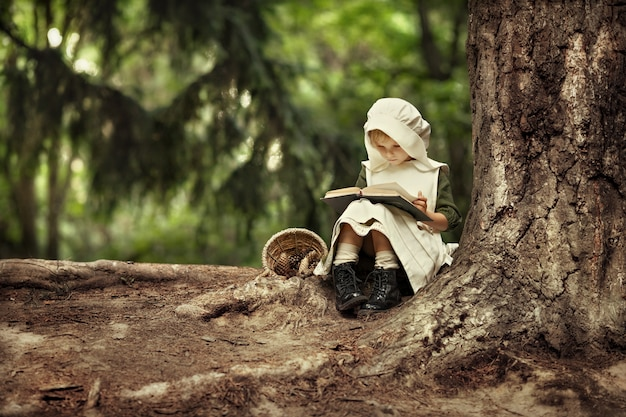 Magic childhood! miracles happen. a little fairy girl walks through an incredibly beautiful green forest. bedtime stories.