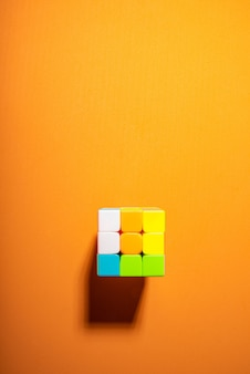 Magic cube on an orange eva surface and hard light, top view.