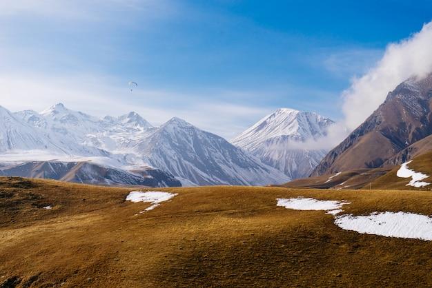 Волшебная чарующая природа, высокие горы, покрытые белым снегом, под голубым небом