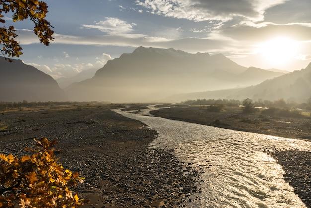魔法の魅惑的な自然、夕日の光の中の山や丘、川