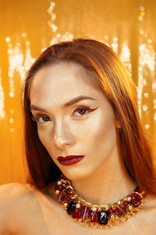 골드에서 마법 소녀 초상화입니다. 황금 메이크업, 스튜디오 촬영, 컬러 클로즈업 초상화. 완벽한 밝은 메이크업, 붉은 입술, 황금 적갈색 보석을 가진 뷰티 모델 소녀. 섹시 레이디 메이크업 홀리데이 파티.