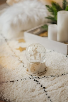 Magic glass snow globe with deer and a garland on a fluffy carpet in a bright interior.