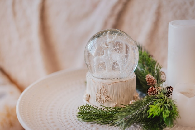 Magic glass snow globe with deer and spruce branches.