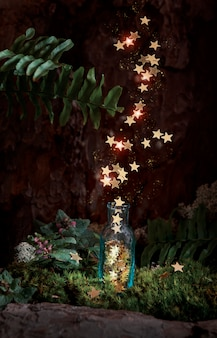 Magic glitter stars fly out of a glass bottle that stands at the foot of a tree in moss