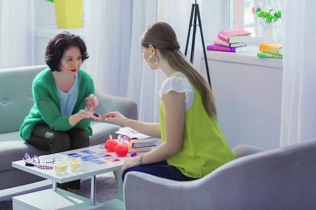 Магический предмет. милая приятная женщина разговаривает со своим клиентом, держа в руках волшебную идею