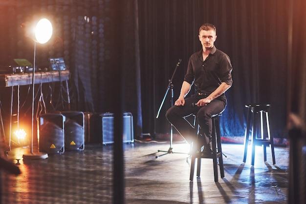 Aspetto magico. giovane bello in vestiti neri che si siede sulla sedia vicino in camera oscura con luce.
