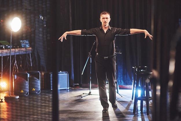 魔法のような外観。光の暗い部屋の近くの椅子に座っている黒い服を着たハンサムな若い男。