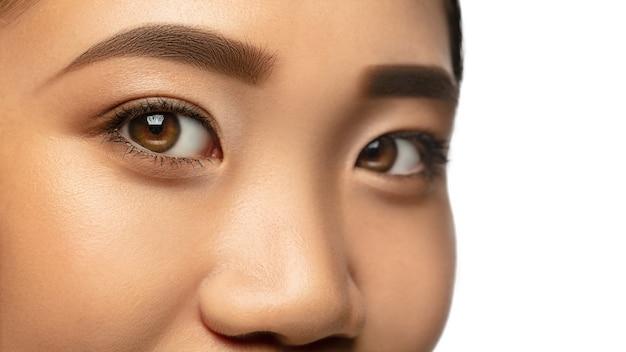 마법의 모습. 흰색으로 격리된 아름다운 아시아 여성의 눈과 뺨을 닫습니다.