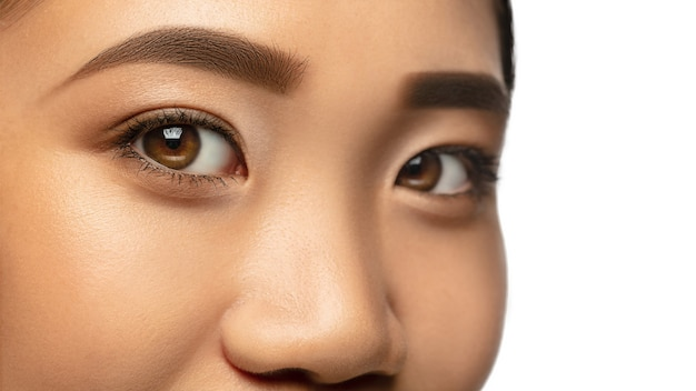 Magic looks. close up eyes and cheeks of beautiful asian woman isolated on white.