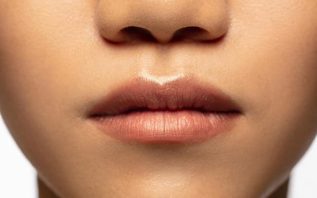 마법의 모습. 흰색으로 격리된 아름다운 아시아 여성의 입술과 뺨을 닫습니다.