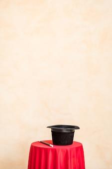 복사 공간 그런 지 벽 벽에 테이블에 마술 지팡이와 검은 모자