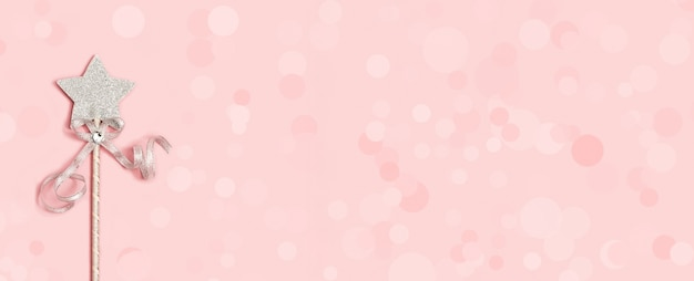 Magic wand, bright silver star with shine on soft pink