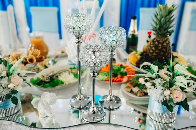 Magic wedding decor on the tables of the bride and groom, white and blue color
