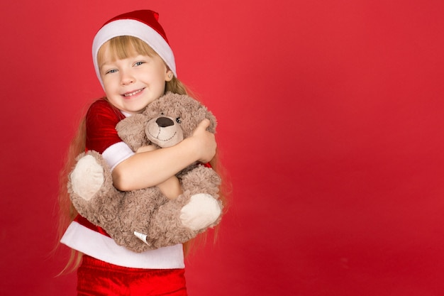 Magic winter. horizontal portrait of a beautiful little girl laughing happily hugging her teddy bear