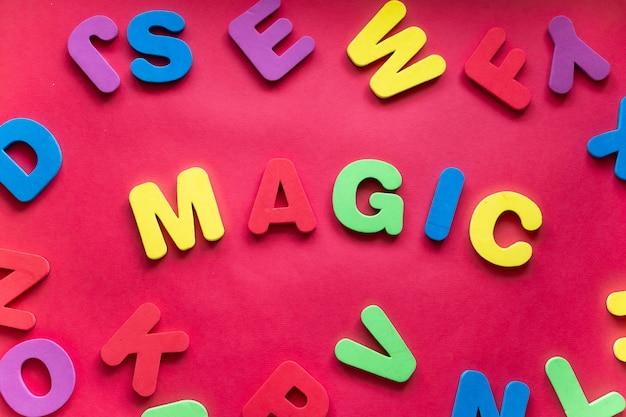 Слово magic из пластиковых магнитных букв на красном фоне