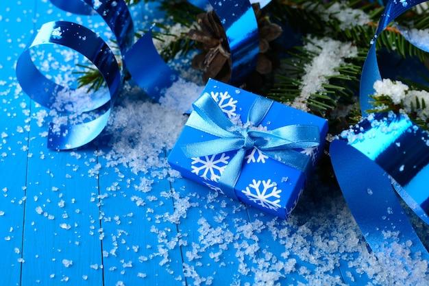 리본과 눈에 소나무 나무 가지와 파란색 선물 상자의 마법의 배열.