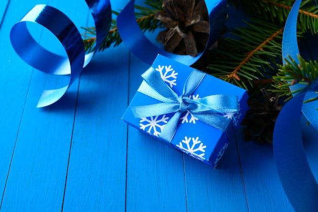 리본과 소나무 나뭇 가지가있는 파란색 선물 상자의 마법 배열