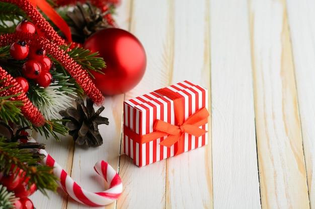 소나무 신선한 가지와 크리스마스 장식으로 작은 선물 상자와 사탕 지팡이의 마법 배열.
