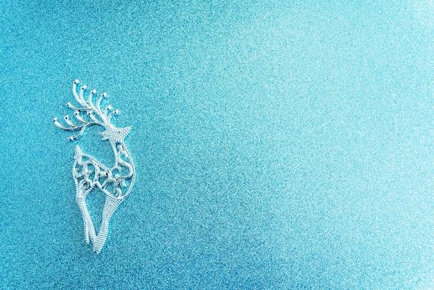 青いボケ背景の前に鹿と雪と魔法のクリスマス紙冬の背景。