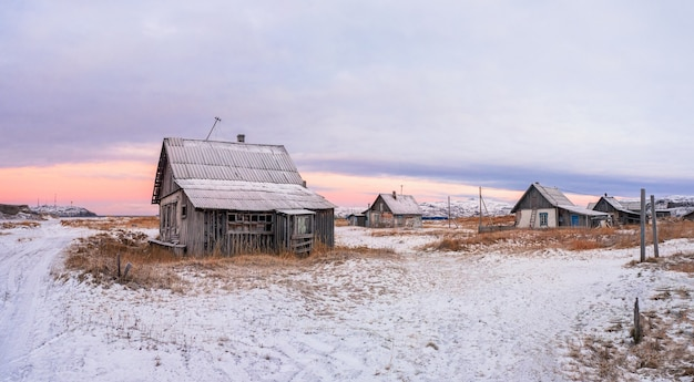 極北の古い村と魔法のようなカラフルな夕日。テリベルカの冬の街の眺め。ロシア。