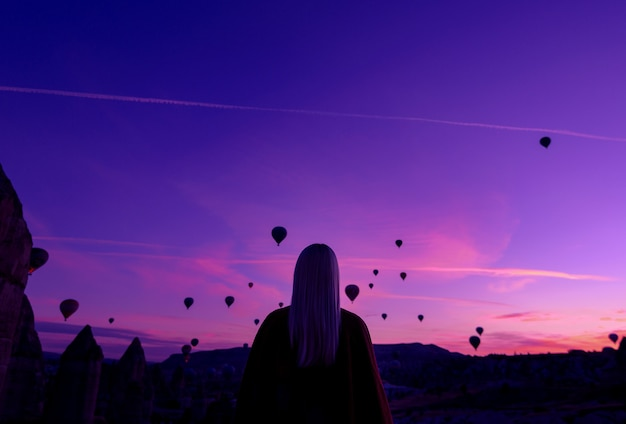 Magical dawn in goreme cappadocia turkey. a girl in a canyon in traditional clothes surrounded by balloons in the rays of the rising sun