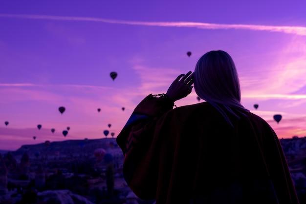 Волшебный рассвет в гереме каппадокия, турция. девушка в каньоне в традиционной одежде в окружении воздушных шаров в лучах восходящего солнца