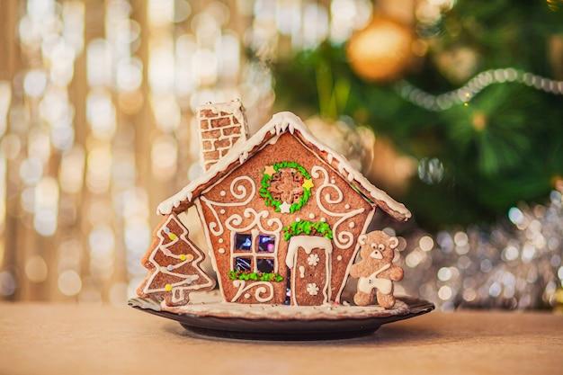 松の枝と金色と銀色のライトが背景にある魔法の自家製ジンジャーブレッドハウス。メリークリスマスと新年あけましておめでとうございますご挨拶とはがき