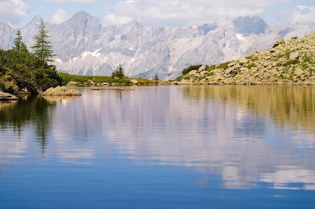 アルプスヨーロッパの山の湖と魔法の牧歌的な風景。アルプスの緑の丘の観光トレイル。美しい岩と山頂の素晴らしい景色を眺めることができます。素晴らしい晴れた日は山の湖にあります