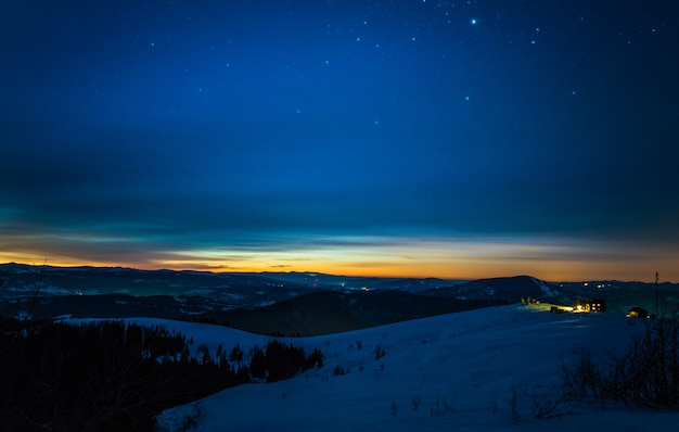 The magical landscape of coniferous forest growing among the hills in winter against a blue starry sky and a crimson sunset