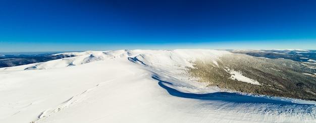 澄んだ青い空と晴れた日のスキー場の雪に覆われた山々の美しい丘の魔法のパノラマ。冬の観光の概念。コピースペース