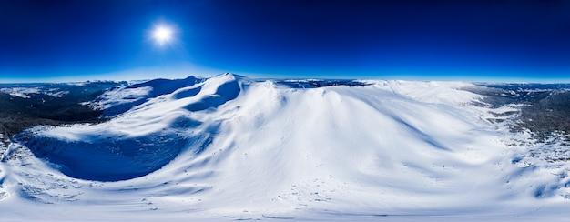 澄んだ青い空と晴れた日にスキー場の雪に覆われた山の美しい丘の魔法のパノラマ