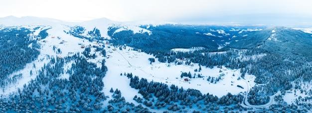 맑고 푸른 하늘과 맑은 날에 스키 슬로프에 눈으로 덮여 산의 아름다운 언덕의 마법의 파노라마