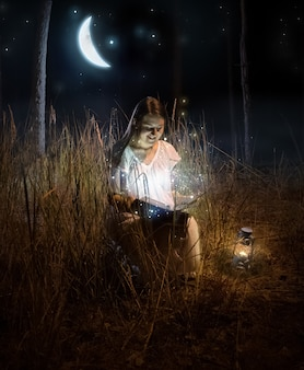 Magical photo of beautiful woman sitting at night forest and reading fairy tale book