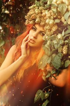 屋外で頭にホップの花輪を持つ美しい若い女性の魔法の肖像画