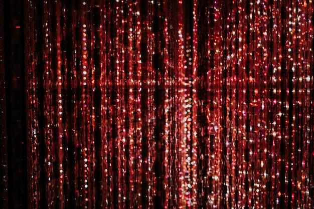 パーティーやお祝いのための魔法の赤いライトボケテクスチャ。輝く光のガーランド
