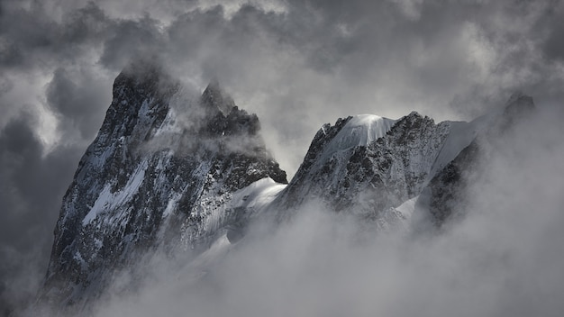 Colpo magico di un bellissimo picco di montagna innevata coperto di nuvole.