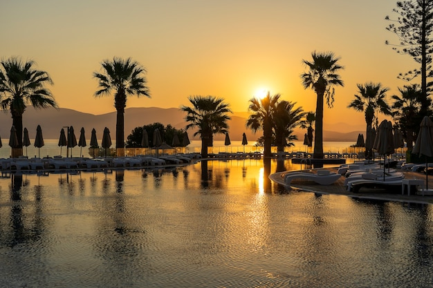 Magical sunrise with silhouette coconut palm tree and swimming pool in luxury hotel resort near sea. beautiful morning seascape. turkey