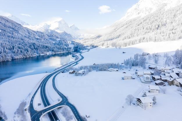 Magico lago invernale svizzero nel centro delle alpi circondato dalla foresta ricoperta di neve
